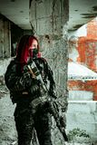 Airsoft red-head woman in uniform and put down machine gun. Soldier standing on balkony. Vertical photo