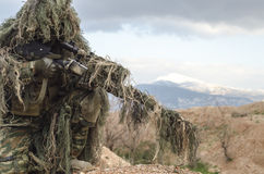 Airsoft sniper on hill rocks. Airsoft sniper soldier engage target Royalty Free Stock Photos