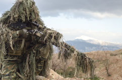 Airsoft sniper on hill rocks Stock Photo