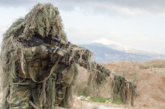 Airsoft sniper on hill rocks. Airsoft sniper soldier engage target Royalty Free Stock Photography