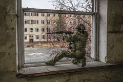 Airsoft sniper at the window. Against the background of the ruins of buildings. Soldier of the army. Military Royalty Free Stock Image
