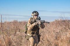 Airsoft-Soldat, der in Felder mit Gewehr läuft Stockfoto