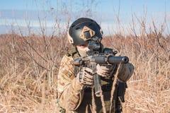 Airsoft-Soldat, der mit Gewehr in den Händen aufwirft Lizenzfreies Stockfoto