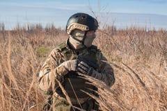 Airsoft-Soldat, der mit Pistole in den Händen aufwirft Stockfotos