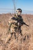 Airsoft-Soldatlüge bei der Aufstellung mit Gewehr Stockfotografie