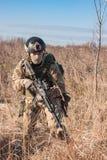 Airsoft-Soldatlüge bei der Aufstellung mit Gewehr Lizenzfreies Stockfoto