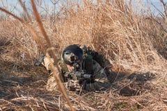 Airsoft-Soldatlüge in den Büschen Stockfotografie