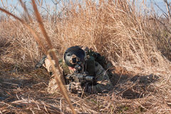 Airsoft soldier lie in bushes Stock Photography