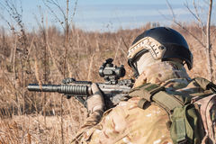 Airsoft soldier lie in posing with rifle close up picture Royalty Free Stock Images