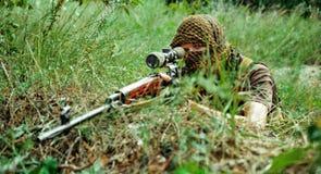 Airsoftmens met optisch gezichts Russisch geweer De terrorist in arafat op gezicht legt op heuvel royalty-vrije stock afbeelding