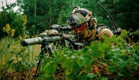 Airsoftmens met optisch gezichtskanon De militair legt op heuvel stock fotografie