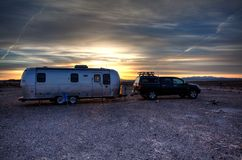 Airstream Retro Travel Trailer parked in the California Desert camping. Airstream RV Travel Trailer camping in the empty California Desert at sunset royalty free stock image