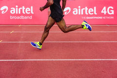Airtel 4G smartphone network. A runner sprinting on the race track ahead of others with Airtel 4G banner behind him. Can be compared to the speed of the network Stock Images