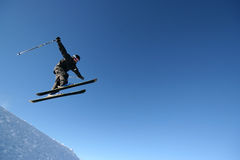 Airtime. A skier in a business-like pinstripe ski suit flies through the air royalty free stock image
