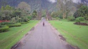 Airview del camino salvaje recto en el medio de la selva, paseos de la motocicleta a continuación, dos personas en una motociclet almacen de metraje de vídeo