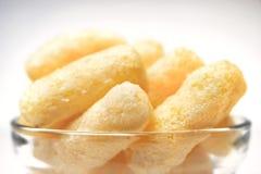 Airy Crisps, Mais-Hauche, Puffcorn-Imbisse in einer Glasschüssel auf klarem Hintergrund Knuspriges gewürzt stießen essfertige Fes lizenzfreie stockfotografie