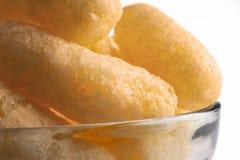 Airy Crisps, sopros do milho, petiscos de Puffcorn em uma bacia de vidro no fundo claro Crocante Flavored soprou deleites prontos imagens de stock
