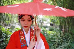 Aisa Chinese woman Peking Beijing Opera Costumes Pavilion garden China traditional role drama play bride hold red Umbrella royalty free stock photo