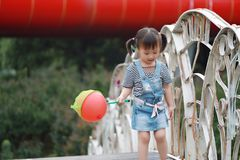 Aisa cute naughty lovely child girl play with balloon have fun outdoor in summer park happy smile happiness funny childhood. A little Asian Chinese girl, have Royalty Free Stock Image