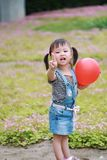 Aisa cute naughty lovely child girl with V pose play with balloon have fun outdoor in summer park happy smile happiness childhood. A little Asian Chinese girl Stock Photography
