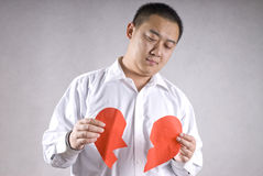 Aisa man with broken heart. A sad man with two pieces of broken heart Royalty Free Stock Images