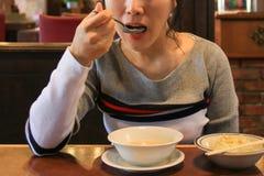 aisan νέα όμορφη γυναίκα που τρώει τη σούπα με το κουτάλι στοκ φωτογραφία με δικαίωμα ελεύθερης χρήσης
