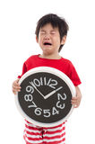 Aisan boy crying and holding clock Royalty Free Stock Photos