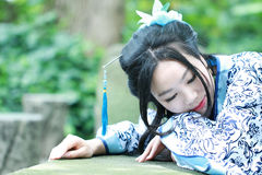 Aisan Chinese woman in traditional Blue and white Hanfu dress, kill time in a famous garden Stock Photography