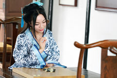 Aisan Chinese woman in traditional Blue and white Hanfu dress play the game of go Stock Photos