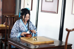 Aisan Chinese woman in traditional Blue and white Hanfu dress play the game of go. Chinese woman in traditional Hanfu dress go go at Qiyuan Garden. weiqi, a game Stock Image