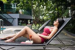 Free Aisan Girl Relax On Pool Chair To Get Tan Stock Image - 193630361