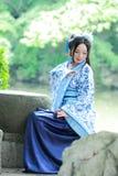 Aisan klär dödar den kinesiska kvinnan i traditionella blått och vit Hanfu, tid i en berömd trädgård Royaltyfri Fotografi