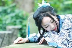 Aisan klär dödar den kinesiska kvinnan i traditionella blått och vit Hanfu, tid i en berömd trädgård Arkivbild