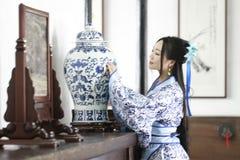 Aisan klär står den kinesiska kvinnan i traditionella blått och vit Hanfu, vid en forntida tabell Royaltyfri Bild