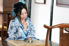 Aisan spelar den kinesiska kvinnan i den traditionella blått- och vitHanfu klänningen leken av går Arkivfoton