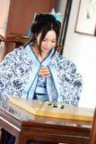 Aisan spelar den kinesiska kvinnan i den traditionella blått- och vitHanfu klänningen leken av går Royaltyfri Foto
