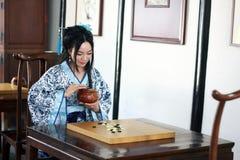 Aisan spelar den kinesiska kvinnan i den traditionella blått- och vitHanfu klänningen leken av går Arkivbild