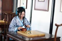 Aisan spelar den kinesiska kvinnan i den traditionella blått- och vitHanfu klänningen leken av går Fotografering för Bildbyråer