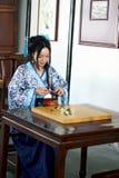Aisan spelar den kinesiska kvinnan i den traditionella blått- och vitHanfu klänningen leken av går Royaltyfria Bilder