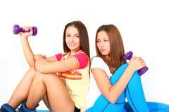 Aislado dos muchachas de la aptitud con las pesas de gimnasia Fotos de archivo libres de regalías