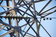 Aislador de alto voltaje y un fragmento del metal del pilón de la electricidad Imagen de archivo