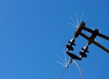 Aislador eléctrico de alto voltaje de la línea eléctrica contra azul Imagen de archivo