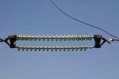 Aisladores de alto voltaje de la transmisión contra el cielo azul Imagenes de archivo