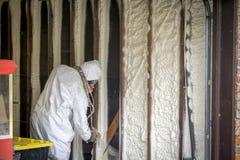 Aislamiento cerrado de rociadura de la espuma del espray de la célula del trabajador en una pared casera imagen de archivo libre de regalías