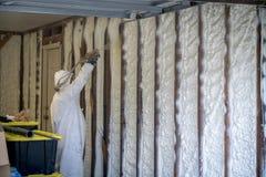 Aislamiento cerrado de rociadura de la espuma del espray de la célula del trabajador en una pared casera fotografía de archivo