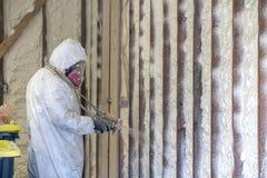 Aislamiento cerrado de rociadura de la espuma del espray de la célula del trabajador en una pared casera foto de archivo libre de regalías