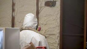 Aislamiento cerrado de rociadura de la espuma del espray de la célula del trabajador en una pared casera almacen de video