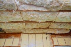 Aislamiento de la fibra de vidrio instalado en el techo que se inclina de una nueva casa de marco Imagen de archivo
