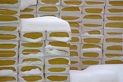 Aislamiento de las lanas minerales que embala debajo de la nieve imagen de archivo