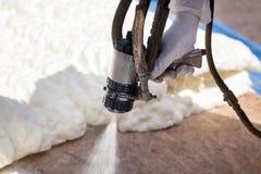 Aislamiento de rociadura de la espuma del técnico usando el arma de espray componente plural fotografía de archivo